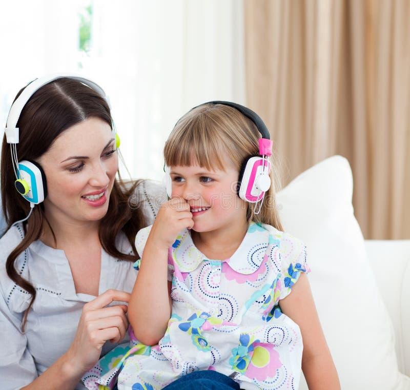 Moeder en haar dochter het luisteren muziek stock afbeeldingen
