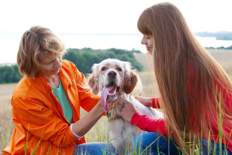 Moeder en haar dochter met hond in openlucht stock afbeeldingen
