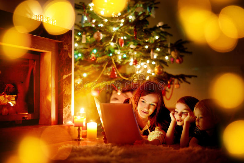 Moeder en haar dochters die een boek lezen stock afbeeldingen