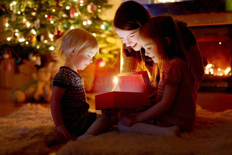Moeder en haar dochters die een Kerstmisgift openen royalty-vrije stock foto's