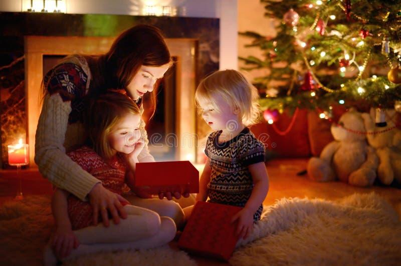 Moeder en haar dochters die een Kerstmisgift openen royalty-vrije stock afbeelding