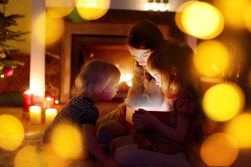 Moeder en haar dochters die een Kerstmisgift openen royalty-vrije stock foto