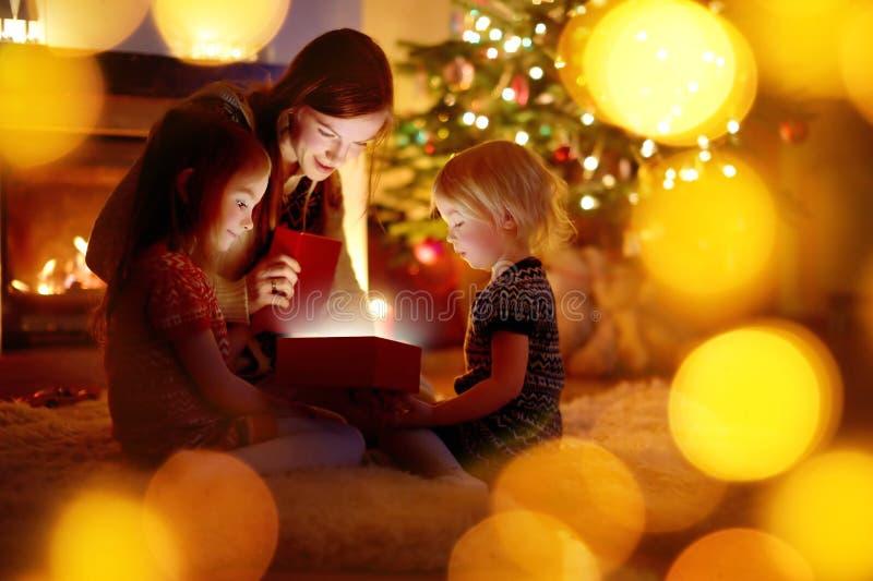 Moeder en haar dochters die een Kerstmisgift openen stock afbeeldingen