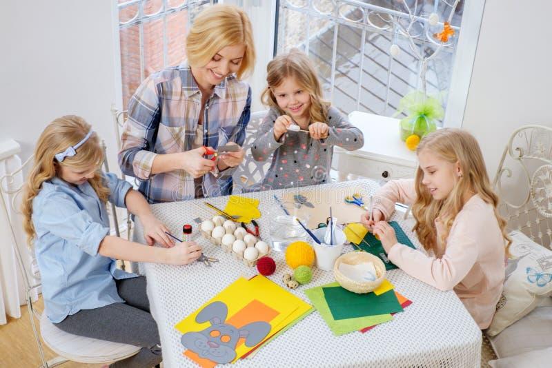Moeder en haar dochters die en paaseieren schilderen verfraaien royalty-vrije stock afbeeldingen