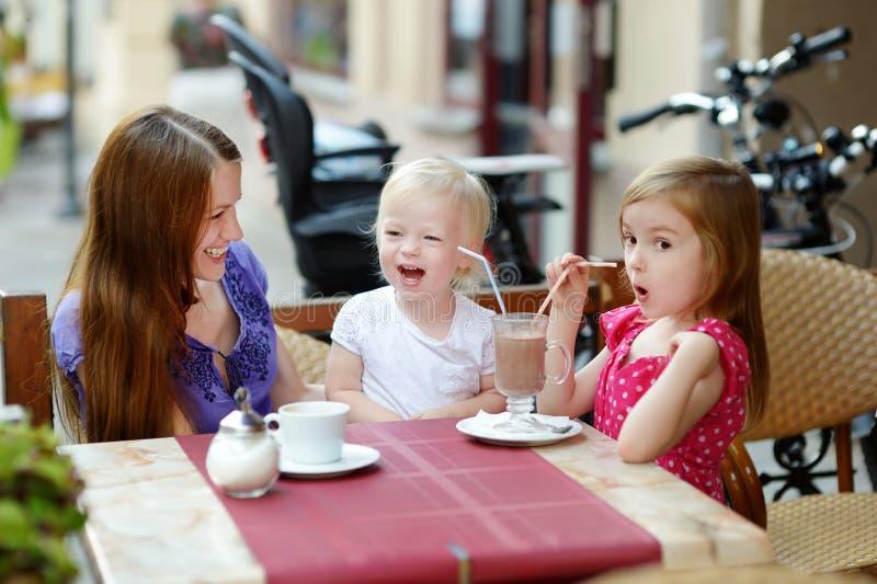 Moeder en haar dochters die in openluchtkoffie ontspannen royalty-vrije stock fotografie