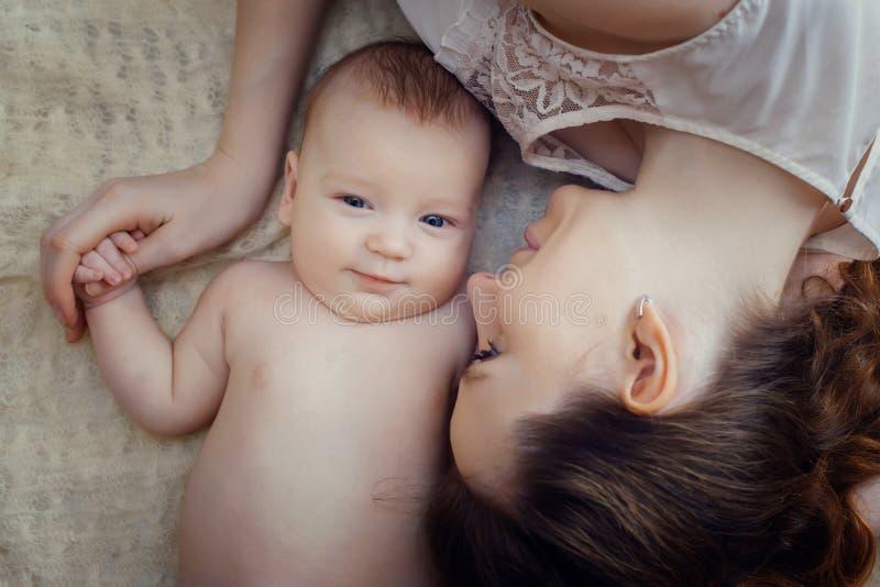 Moeder en haar kind die in het bed liggen stock fotografie