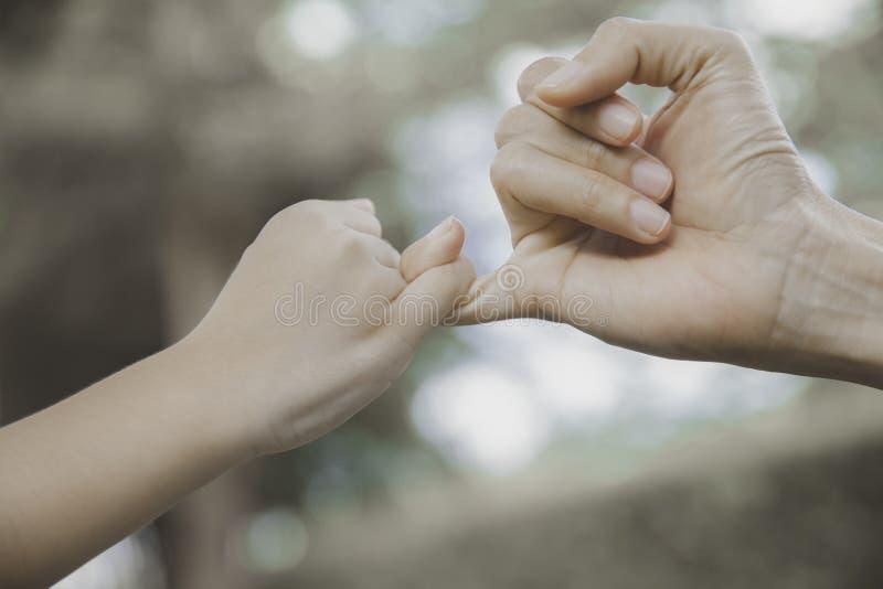 Moeder en haar kind die hun vingers vasthaken om een belofte te maken royalty-vrije stock foto