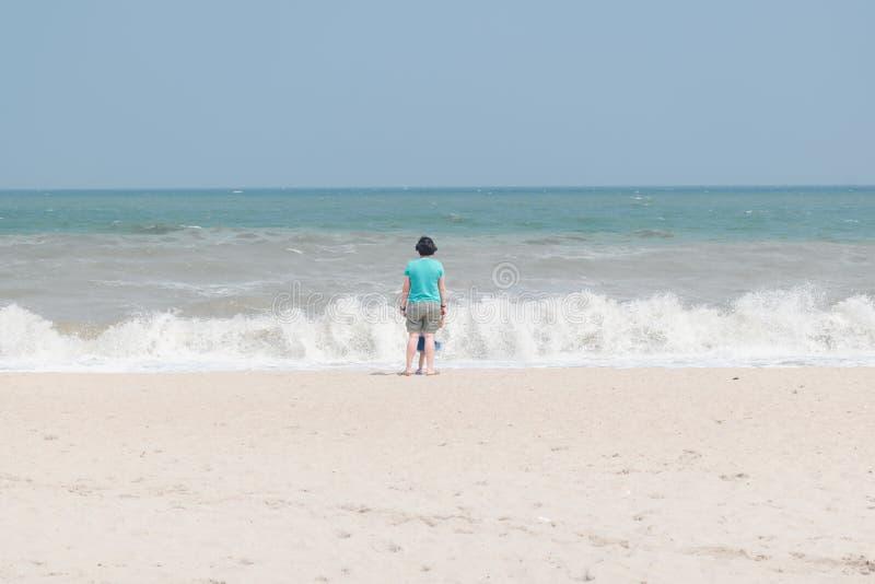 Moeder en haar kind die zich bij strand bevinden royalty-vrije stock afbeelding