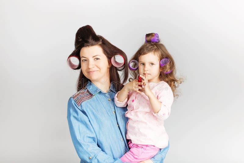 Moeder en haar kinddochter met een lippenstift Portret van een lov royalty-vrije stock fotografie