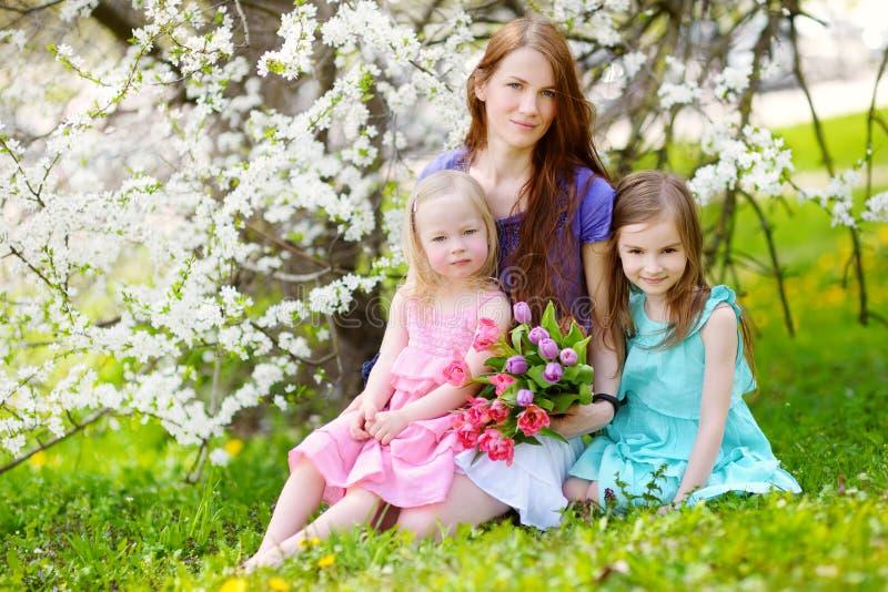 Moeder en haar kinderen in bloeiende kersentuin stock fotografie