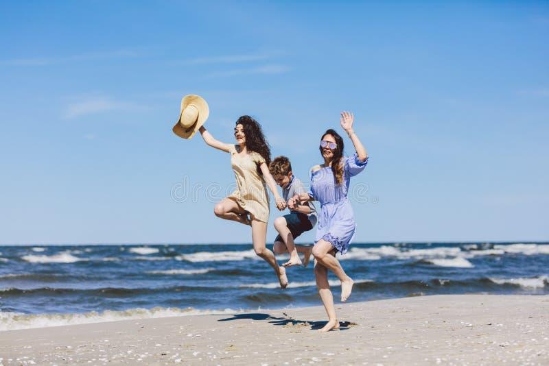Moeder en haar kinderen die hoog op het strand springen royalty-vrije stock afbeelding