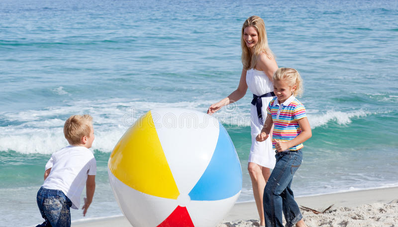 Moeder en haar kinderen die met een bal spelen stock afbeelding