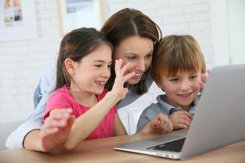 Moeder en haar kinderen op laptop stock fotografie