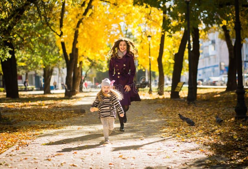 Moeder en haar kindmeisje die samen op de herfstgang in openlucht spelen in aard royalty-vrije stock fotografie