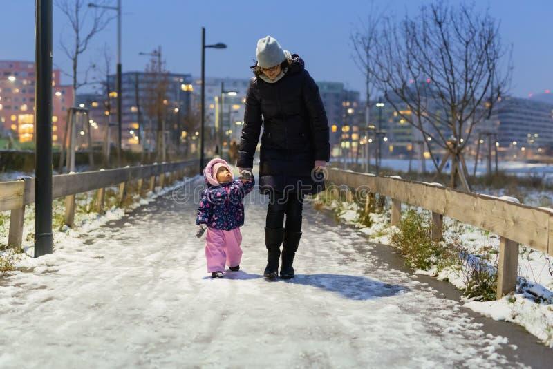 Moeder en haar klein kind die in het sneeuwpark in de winter lopen royalty-vrije stock fotografie