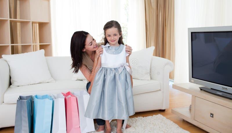 Moeder en haar meisje die op kleding proberen royalty-vrije stock afbeeldingen