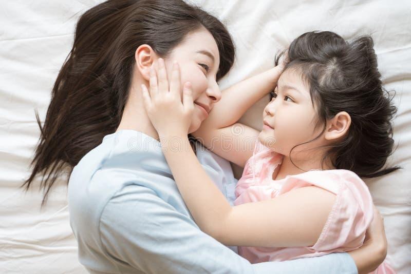 Moeder en haar meisje die van het dochterkind en haar mamma in de slaapkamer koesteren strijken Gelukkige Aziatische Familie royalty-vrije stock foto