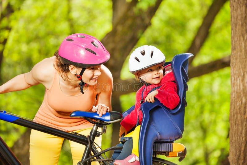 Moeder en haar meisjezitting in fietszetel stock foto's