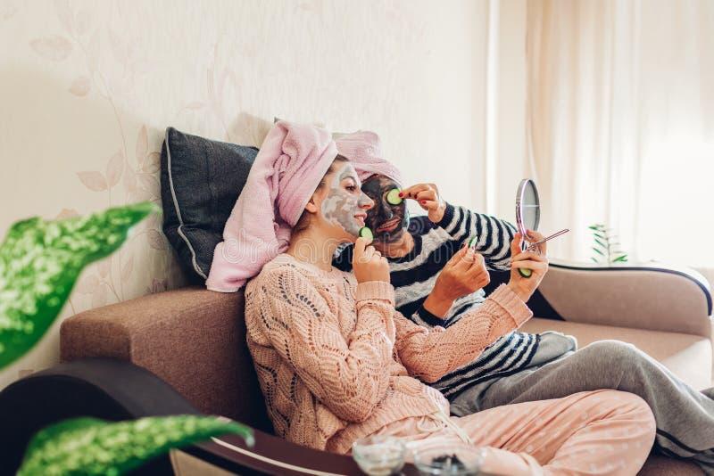 Moeder en haar volwassen dochter die gezichtsmaskers en komkommers op ogen toepassen Vrouwen die en pret thuis koelen hebben stock foto