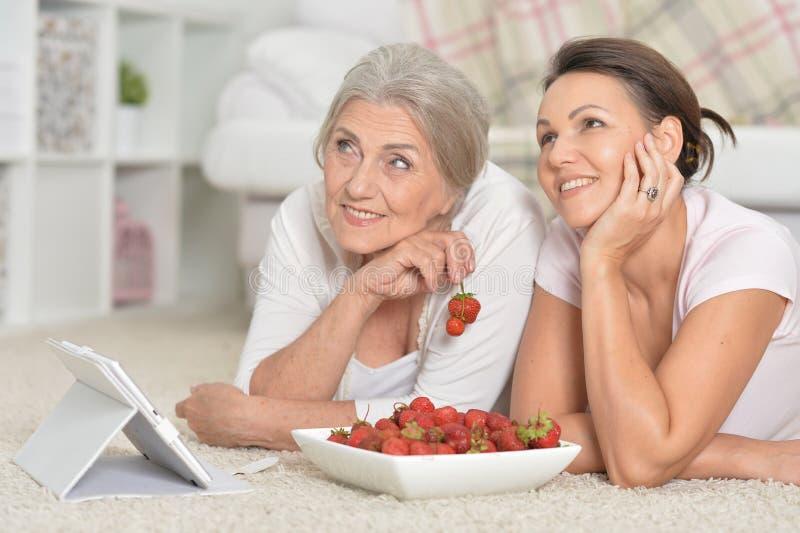 Moeder en haar volwassen dochter die verse aardbeien eten stock afbeelding