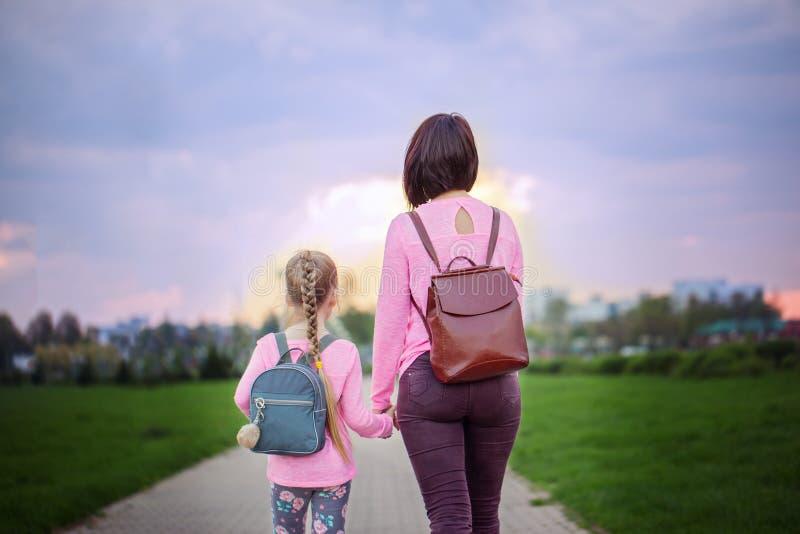 Moeder en haar weinig dauther met rugzak die in de zomerdag lopen Mening van een rug stock afbeelding