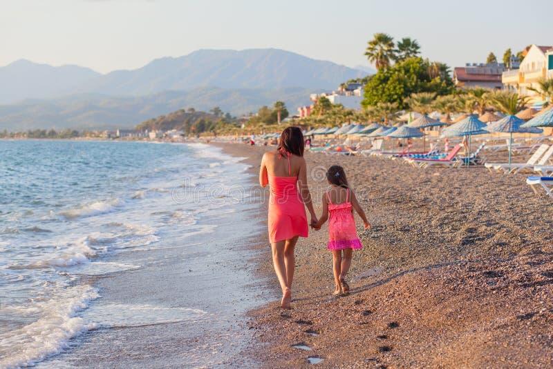 Moeder en haar weinig dochter die langs het strand lopen stock fotografie