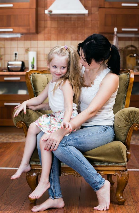 Moeder en haar weinig dochterzitting als voorzitter royalty-vrije stock afbeeldingen