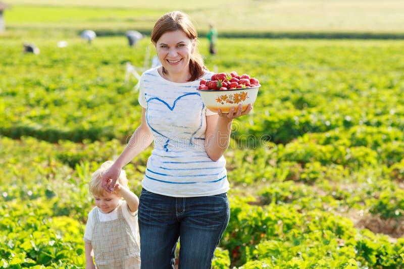 Moeder en haar weinig jong geitjekind op organisch aardbeilandbouwbedrijf stock foto