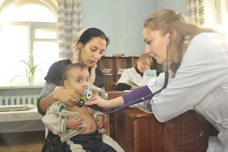 Moeder en haar weinig kind bij een ontvangst met een vrouwelijke pediater arts royalty-vrije stock afbeelding