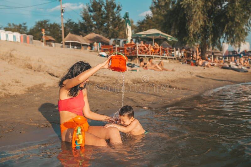 Moeder en haar weinig zoon die met strandspeelgoed spelen in het water royalty-vrije stock afbeelding