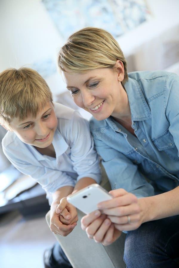 Moeder en haar zoon die op smartphone spelen stock fotografie