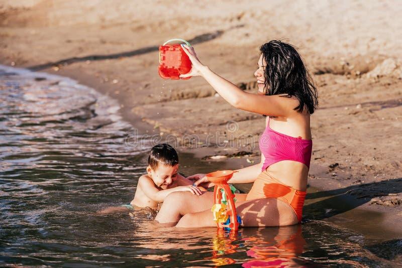 Moeder en haar zoon die op strand spelen royalty-vrije stock foto's