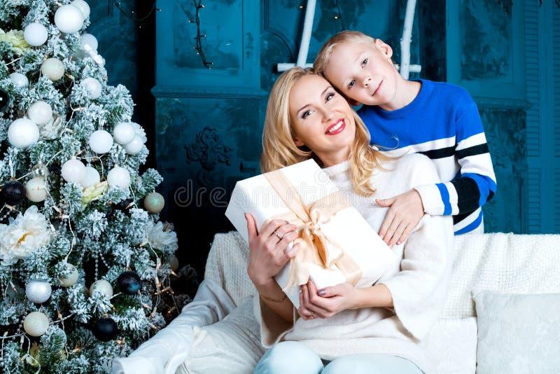 Moeder en haar zoon thuis met een Kerstboom royalty-vrije stock foto's