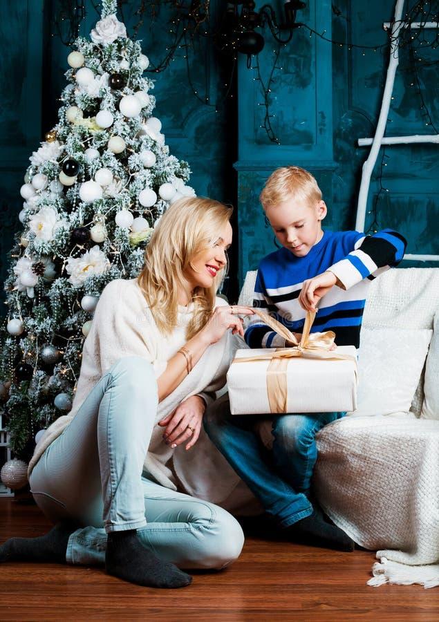 Moeder en haar zoon thuis met een Kerstboom stock afbeeldingen