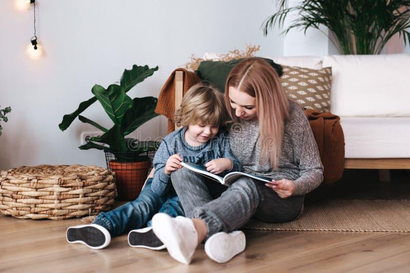 Moeder en het boek van de van de zoonszitting en lezing samen thuis royalty-vrije stock foto