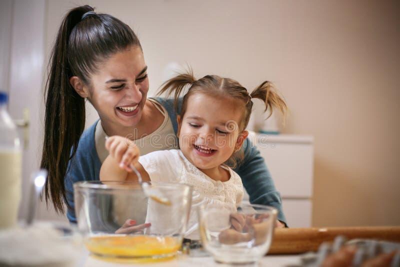 Moeder en het glimlachen meisjesbakselkoekje samen stock fotografie