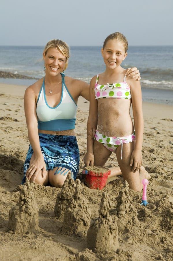 Moeder en het Jonge Zandkasteel van de Bouw van de Dochter stock afbeelding