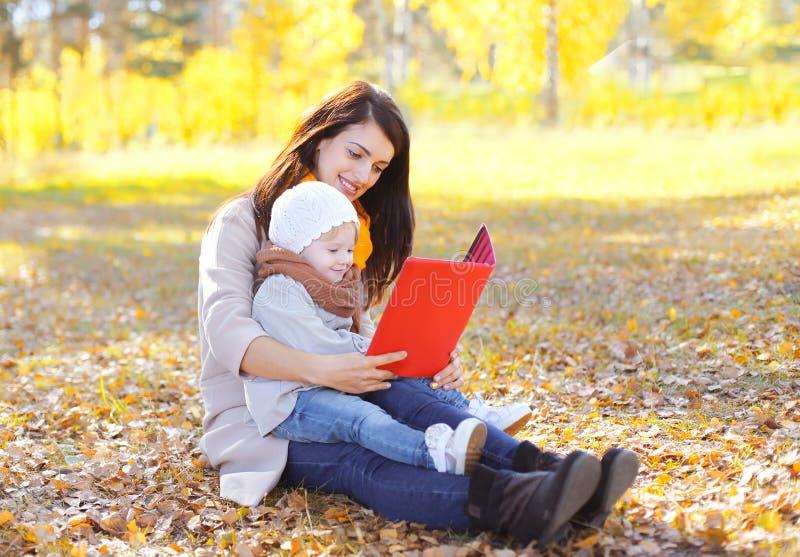 Moeder en het kind die op boek of tabletpc de kijken zitten samen royalty-vrije stock fotografie