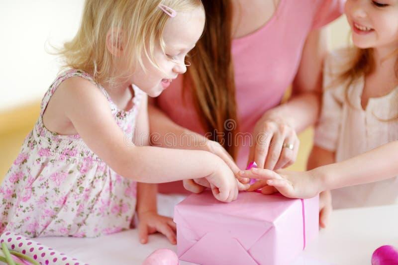 Moeder en het twee dochters die een gift verpakken stock foto