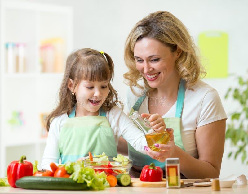 Moeder en jong geitje die gezond voedsel voorbereiden stock afbeelding
