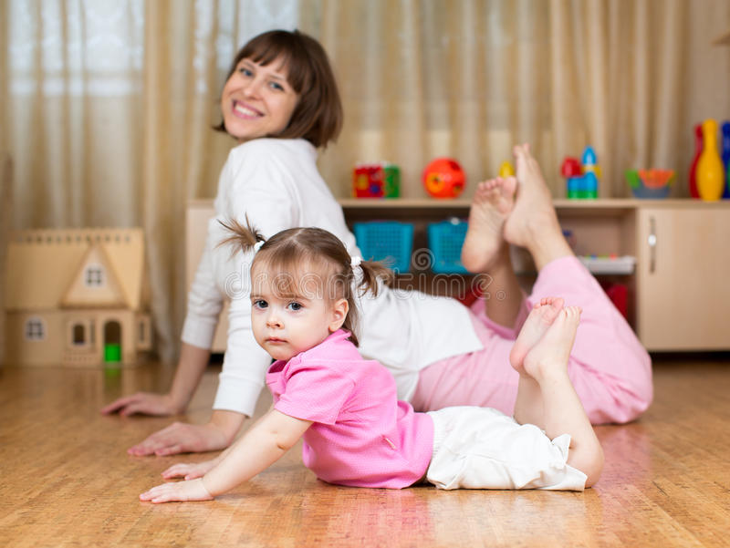 Moeder en jong geitje die oefeningen doen die op de vloer thuis leggen stock foto