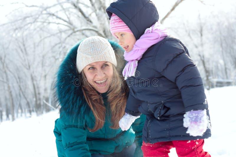 Moeder en jong geitje die pret in openlucht op de winterdag hebben stock afbeeldingen