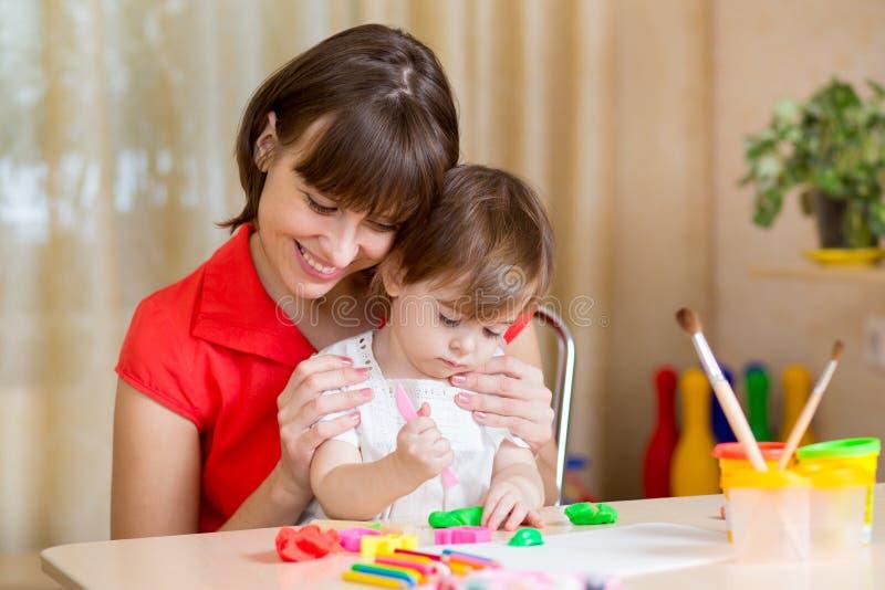 Moeder en jong geitje die thuis spelen stock afbeeldingen