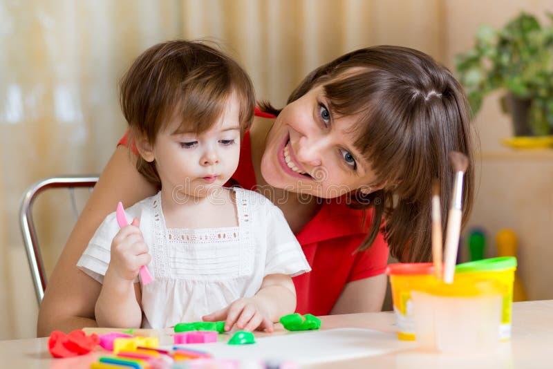 Moeder en jong geitje die thuis spelen stock afbeelding