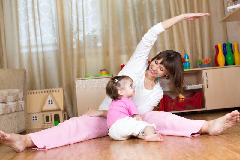 Moeder en jong geitje gymnastiek- doen thuis stock afbeeldingen