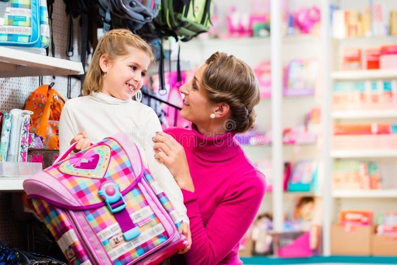 Moeder en jong geitje het kopen schoolschooltas of zak in opslag royalty-vrije stock foto's