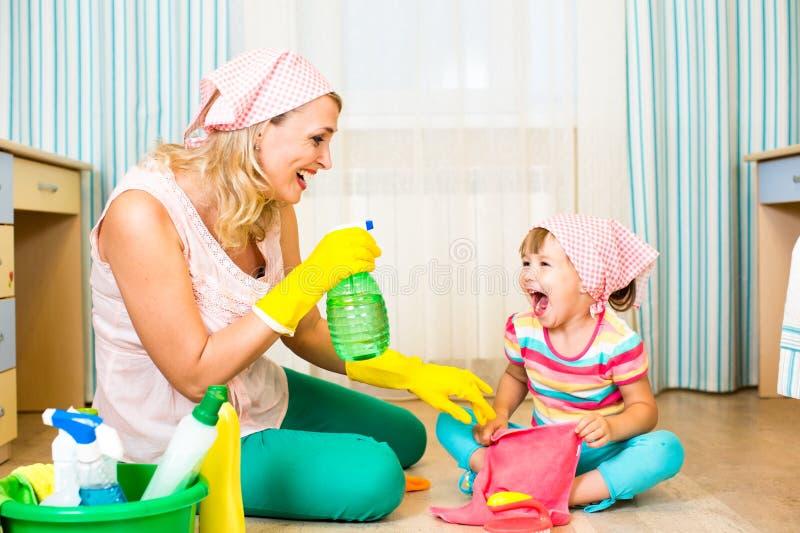 Moeder en jong geitje schoonmakende ruimte en het hebben van pret stock foto