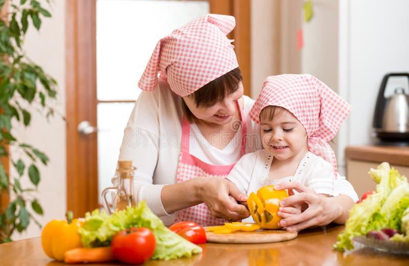 Moeder en jong geitjemeisje die voedsel voorbereiden aan lunch royalty-vrije stock afbeelding