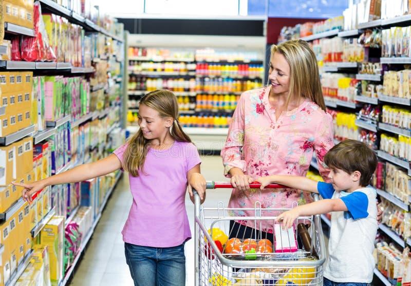 Moeder en jonge geitjes bij de supermarkt royalty-vrije stock afbeelding