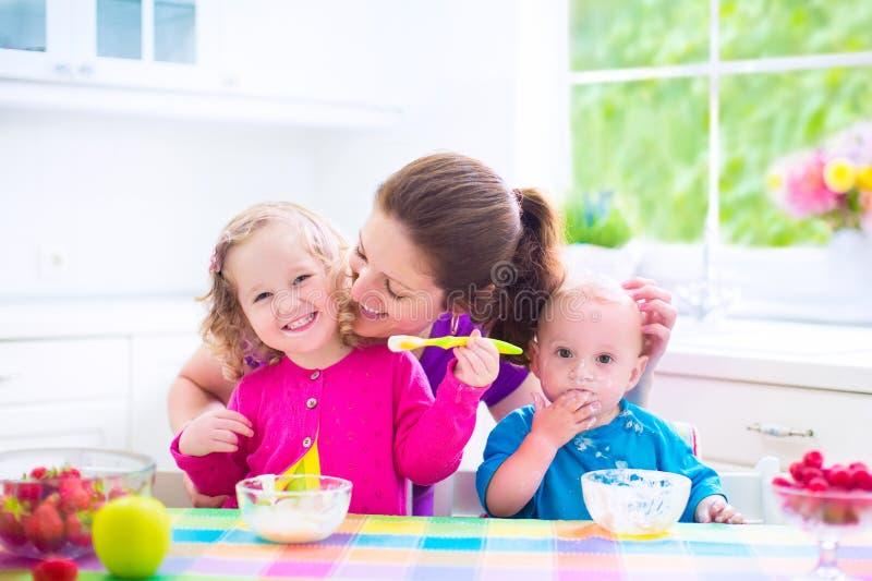 Moeder en jonge geitjes die ontbijt hebben royalty-vrije stock foto